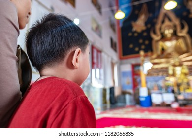 back image of cute small child sitting with mother inside thai buddhist temple facing buddha images on pedestal inside the ordainary hall of the temple