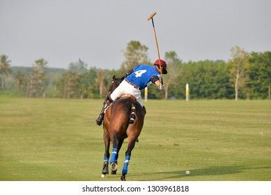 The back image of a horse player riding to hit a ball.