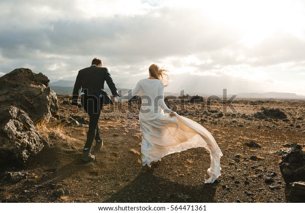 Back of just married couple taking walk on plains of Iceland