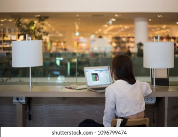 back of lady use laptop on co-working space at modern trade. Behavior of new generation is working at co working space
