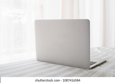 back of laptop on white bed in living room, concept of relax with out work.