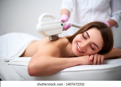 Back laser epilation for young pretty smiling woman in beauty salon. Cosmetologist doing depilation treatment with laser device. Beautician hands in gloves holding hair removal cosmetology hardware.