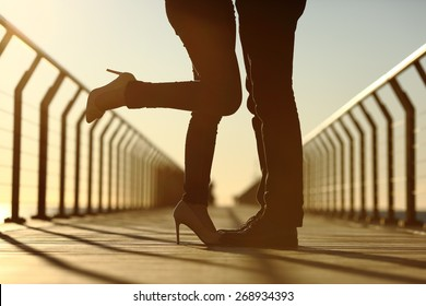 Back light of a couple legs silhouette hugging with love in a bridge at sunset