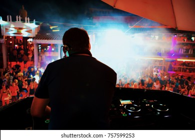 Back light DJ with headphones. Deejay playing music in night club.