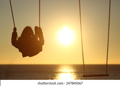 Back light of a lonely woman silhouette swinging at sunset on the beach with another empty swing