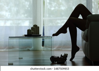 Back light side view silhouette of woman legs and heels sitting on a couch at home