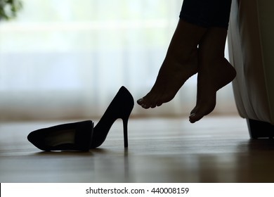 Back light silhouette of a woman feet resting at home with shoes on the floor
