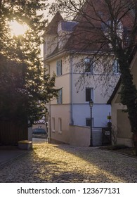 back light in a small village of Germany on a place with cobbles, ancient house and trees