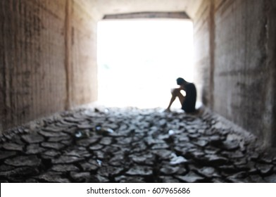 Back light of a teenager depressed sitting inside a dry soil tunnel blur background