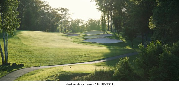 Back lit golf fairway with sand traps viewed from the tee box