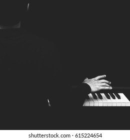 back of male asian musician playing piano, black and white