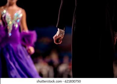 back male dancer athlete in black tailcoat in background of girls dancers
