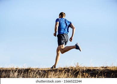 back male runner run in blue shirt and shorts on mountain trail