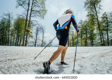 back male skyrunner running mountain snowy trail with trekking poles