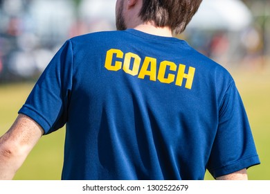 Back of male sport coach wearing blue shirt with COACH yellow text on the back at an outdoor sport field