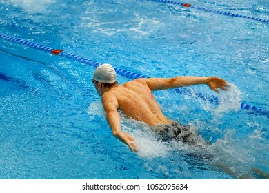 back male swimmer swimming pool butterfly
