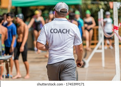 Back of male swimming coach walking on the poolside toward his young swimmers