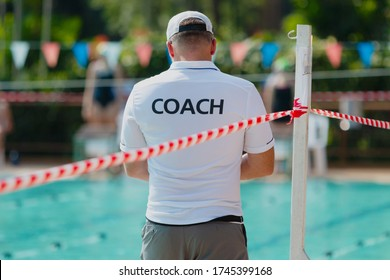 Back of male swimming coach in white coach shirt working at an outdoor swimming pool