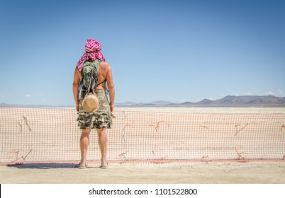 Back of man at burning man standing at fence with costume