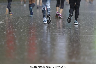 back man Marathon runners focus clear running shoes on the street with rain.