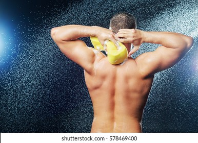 back of a   man taking shower with sponge and foam