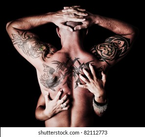 Back of a Man with tattoos with a woman's hands scratching his back