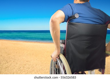 back of a man in wheelchair at beach
