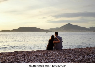 Back of a man and a woman in a black dress sitting by the sea against the backdrop of the setting sun. Romantic couple on a date