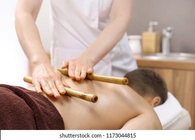 Back massage. The masseur massages the body using bamboo sticks.