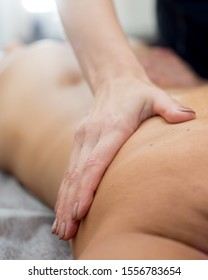 Back massage. Masseuse makes oil massage on female back in spa room