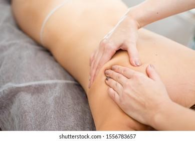 Back massage. Masseuse makes oil massage on female back in spa room