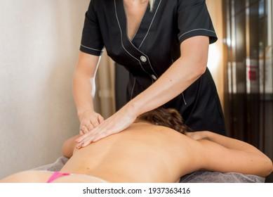 Rückenmassage. Masseuse macht im Wellnessbereich auf weiblicher Rückseite eine Ölmassage