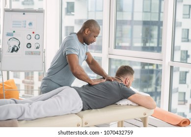 Back massage. Nice strong man standing near his patient while massaging his back