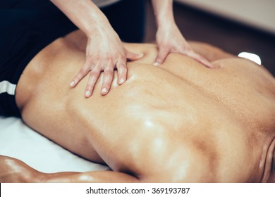 Back massage. Massage therapist massaging lower back region of a male athlete. Toned image