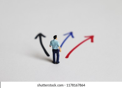 The back of a miniature man standing in front of three forked ways.