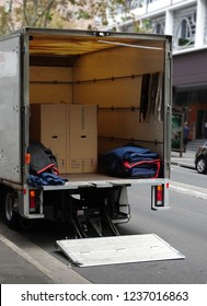 The back of a mover's truck parked on a city street, opened and ready to load.