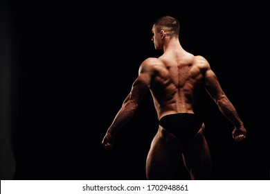 Back muscles in tension. Strong men posing and showing muscles. Great shape before championship. Perfect for sport nutrition promo. Athlete and bodybuilder. Close-ups. Black background.