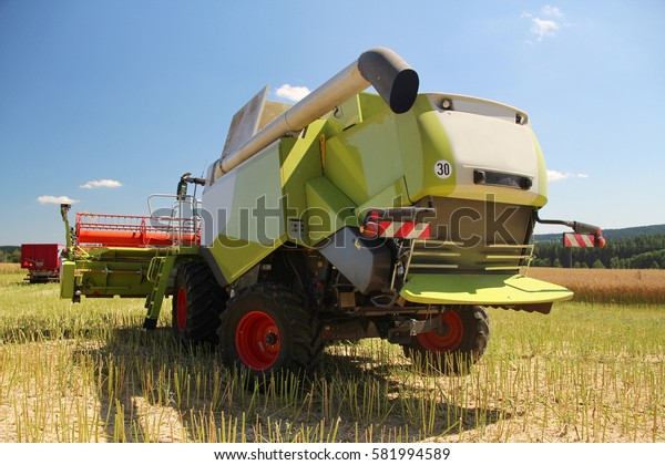 Back of new grain combine on headland, harvest of oilseed rape for bio fuel in hot sunny summer day, fertilized soil with manure, header lifted up