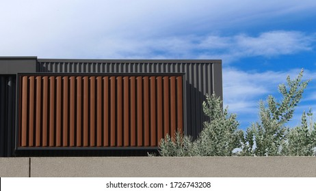 The back of a new townhouse. Pictured is the second storey showing balcony above garage. The structure is metal clad and there are brown exterior aluminium horizontal louver window coverings. Blue sky