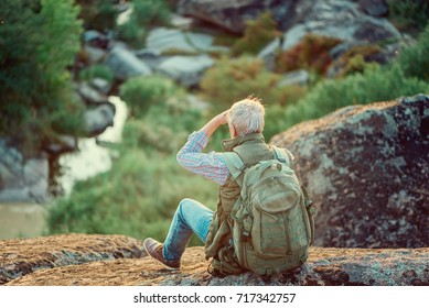 the back of an old male tourist with a gray beard, sitting on rocks against the backdrop of mountains, rocks and woods, the concept of tourism and recreation in old age
