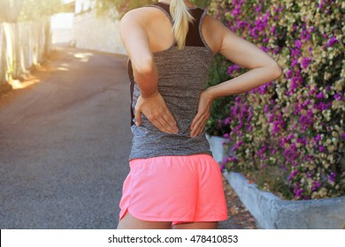 Back Pain. Athletic fitness woman rubbing the muscles of her lower back. Sport injury.