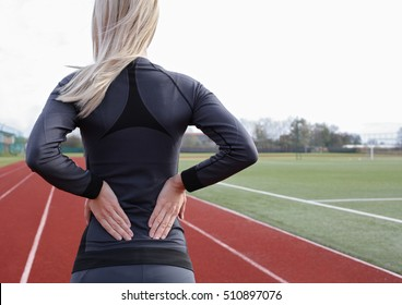 Back Pain. Athletic fitness woman rubbing the muscles of her lower back. Sports exercising injury.