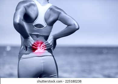 Back pain. Athletic running woman with back injury in sportswear rubbing touching lower back muscles standing on road outside.
