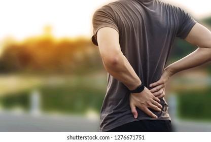 Douleur au dos, gros plan sur un homme a une douleur au dos au coucher du soleil avec un arrière-plan parc ou vue nationale