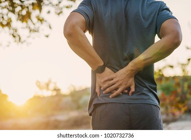 Back pain, close up young man has muscle injury during outdoor exercise