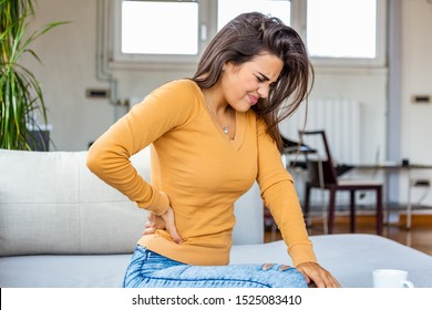 Back Pain. Closeup Of young woman Having Spinal Or Kidney Pain, Backache. Girl Suffering From Painful Feeling, Muscle Or Nerve Pain, Holding Hands On Body. Health Issue Concept.