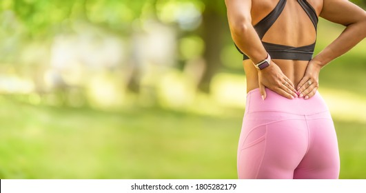 Back pain during sports. Young woman with an athletic figure and a lower back injury.