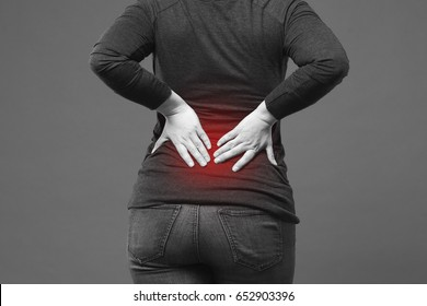 Back pain, kidney inflammation, ache in woman's body close-up on gray background with red dot