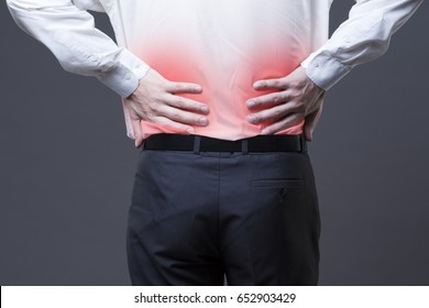 Back pain, kidney inflammation, ache in man's body close-up on gray background with red dot