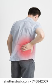 Back pain, kidney inflammation, ache in man's body on gray background with red dot